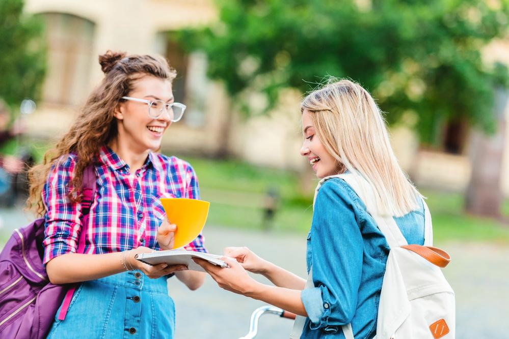Deux étudiantes souriantes échangent des notes.